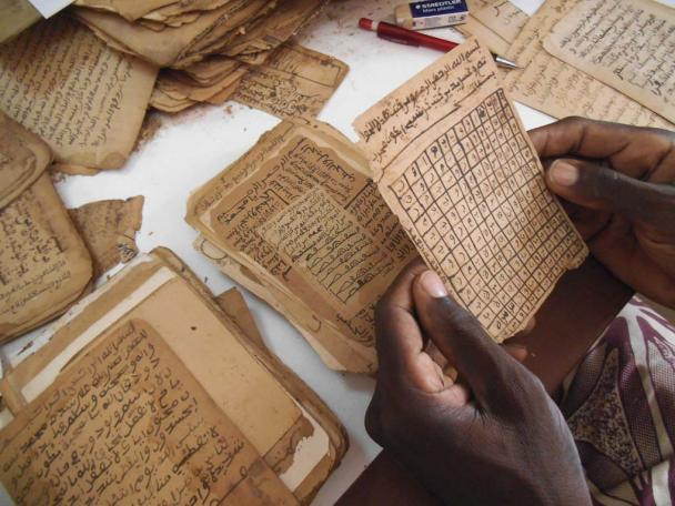 Photograph showing someone holding and reading a manuscript. Djenne, Mali